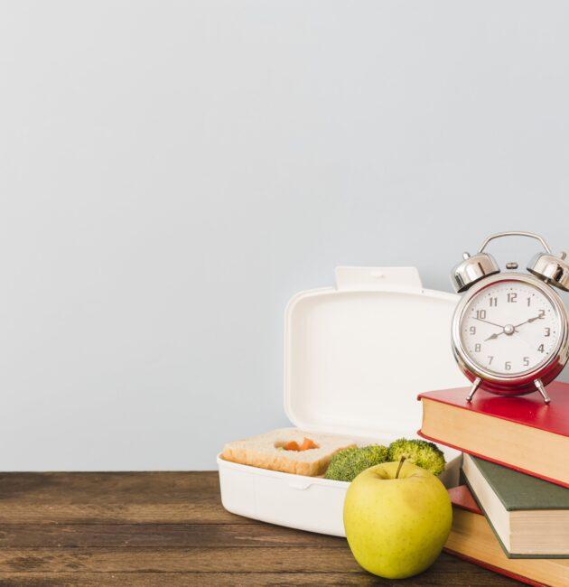 pulkstenis, grāmata, ābols, pusdienu kastīte